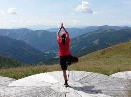 Frau macht Yoga Pose auf einer Wiese am Berg