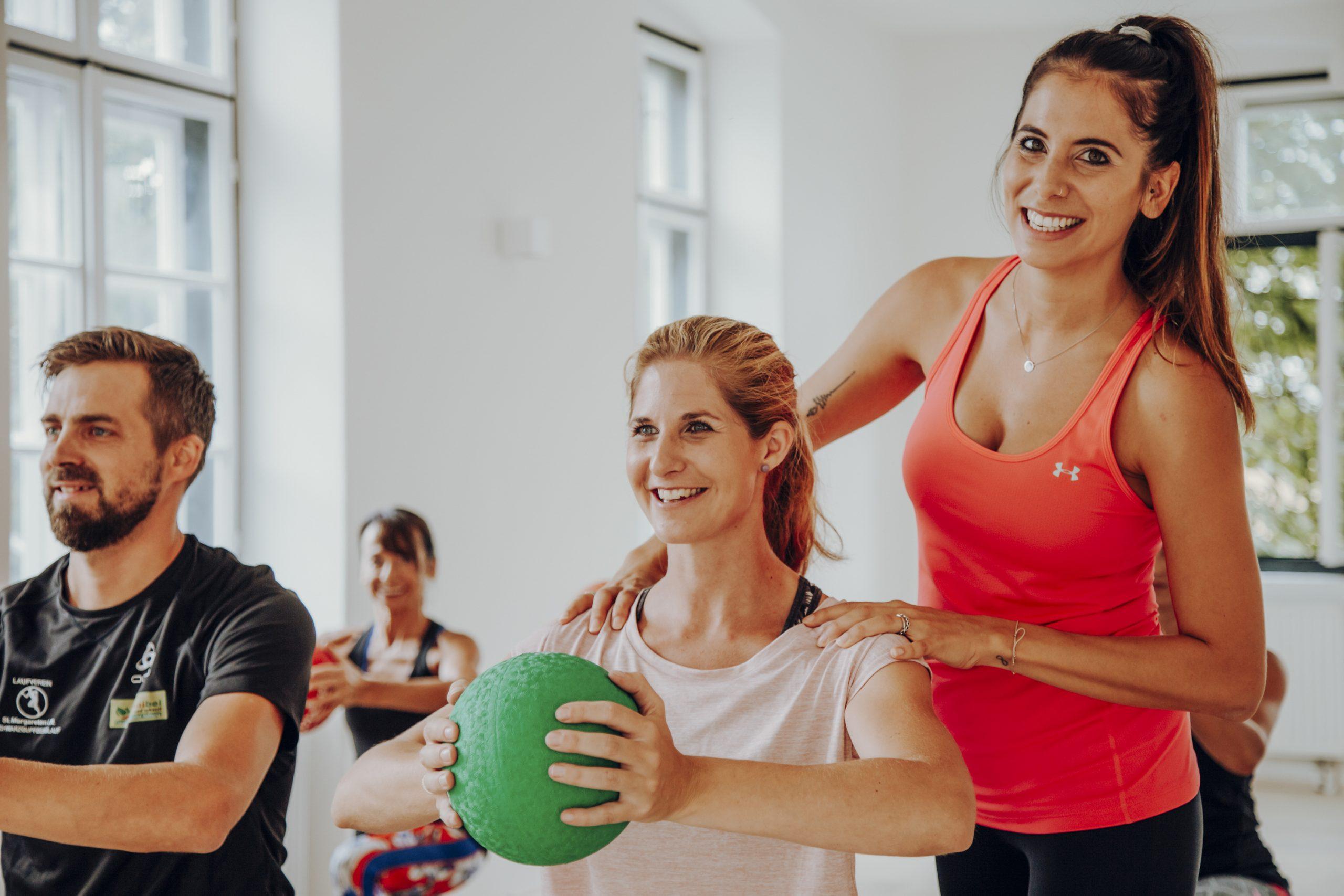 Trainerin steht hinter Frau mit Gymnastikball