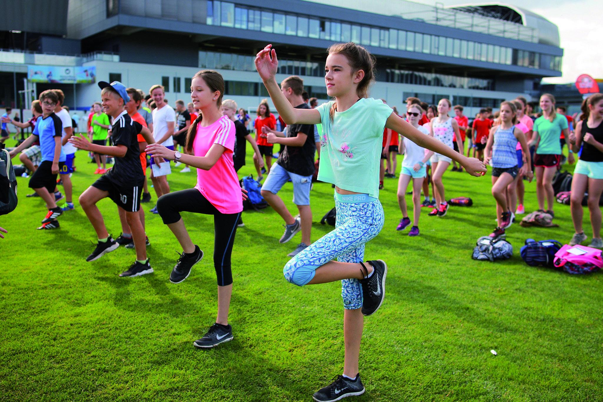 Tanzende Kindergruppe auf Sportplatz